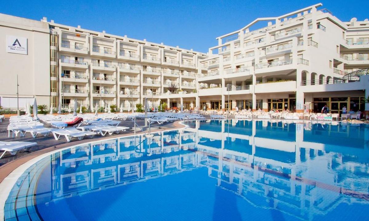 Kæmpe blå pool med liggestole foran hvidt hotel