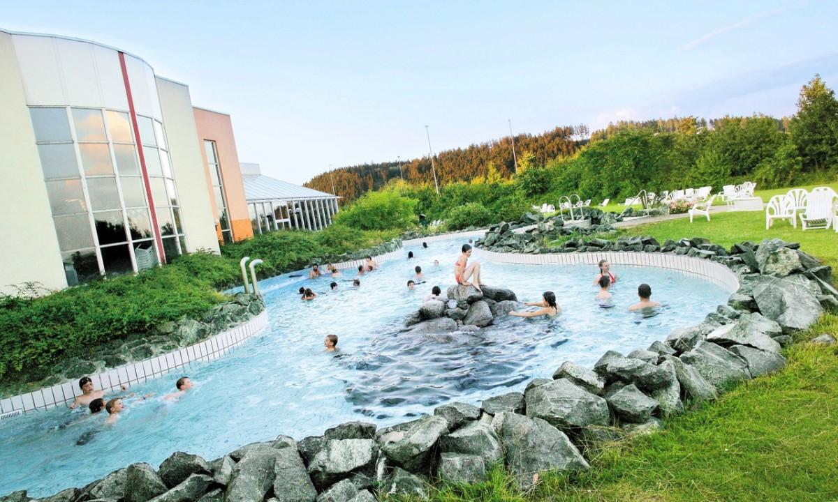Udendørs pool med mennesker omgivet af stengærde