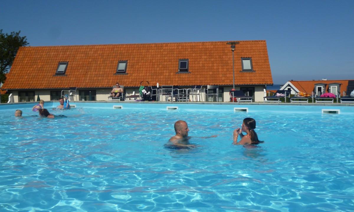 Badegæster i pool foran rødt hus