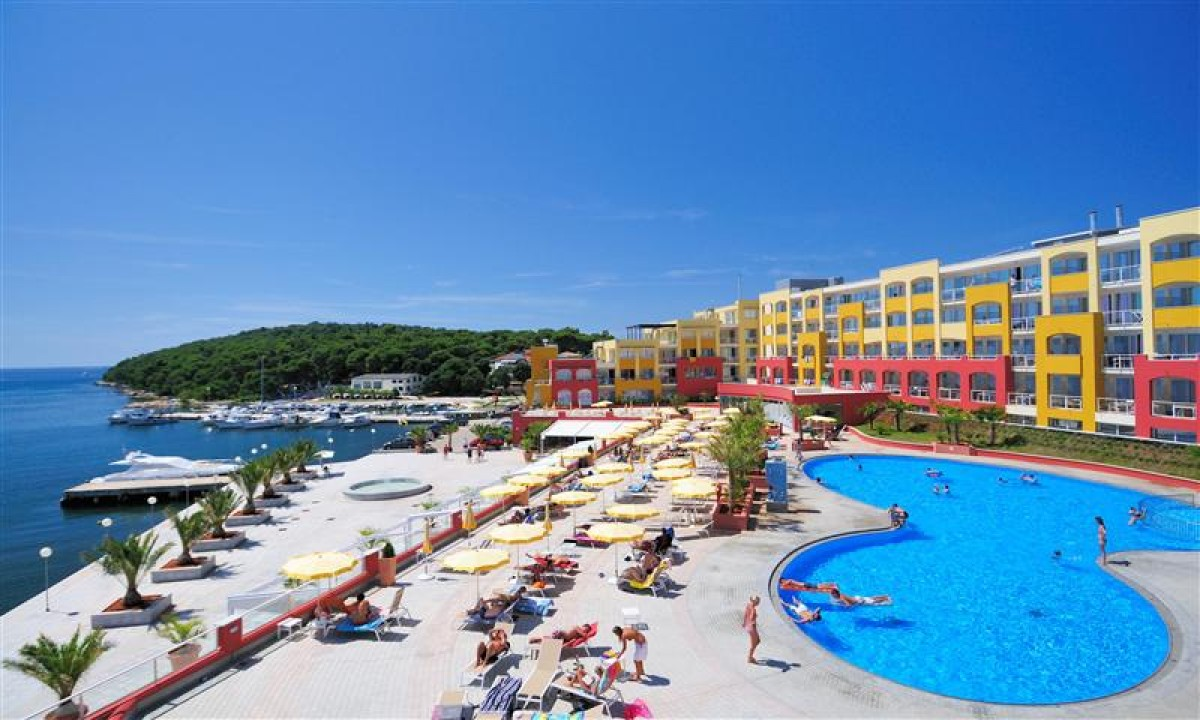 Pool foran gule og røde bygninger med havudsigt