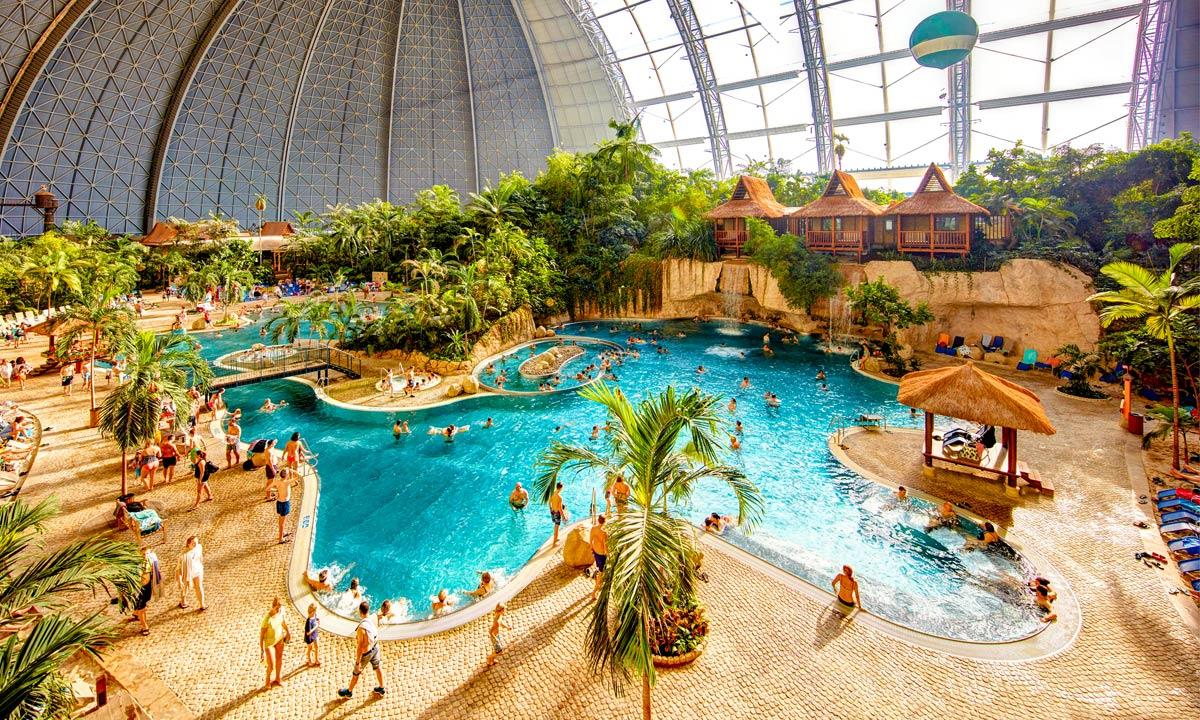 Badeland med pool palmer og badegæster
