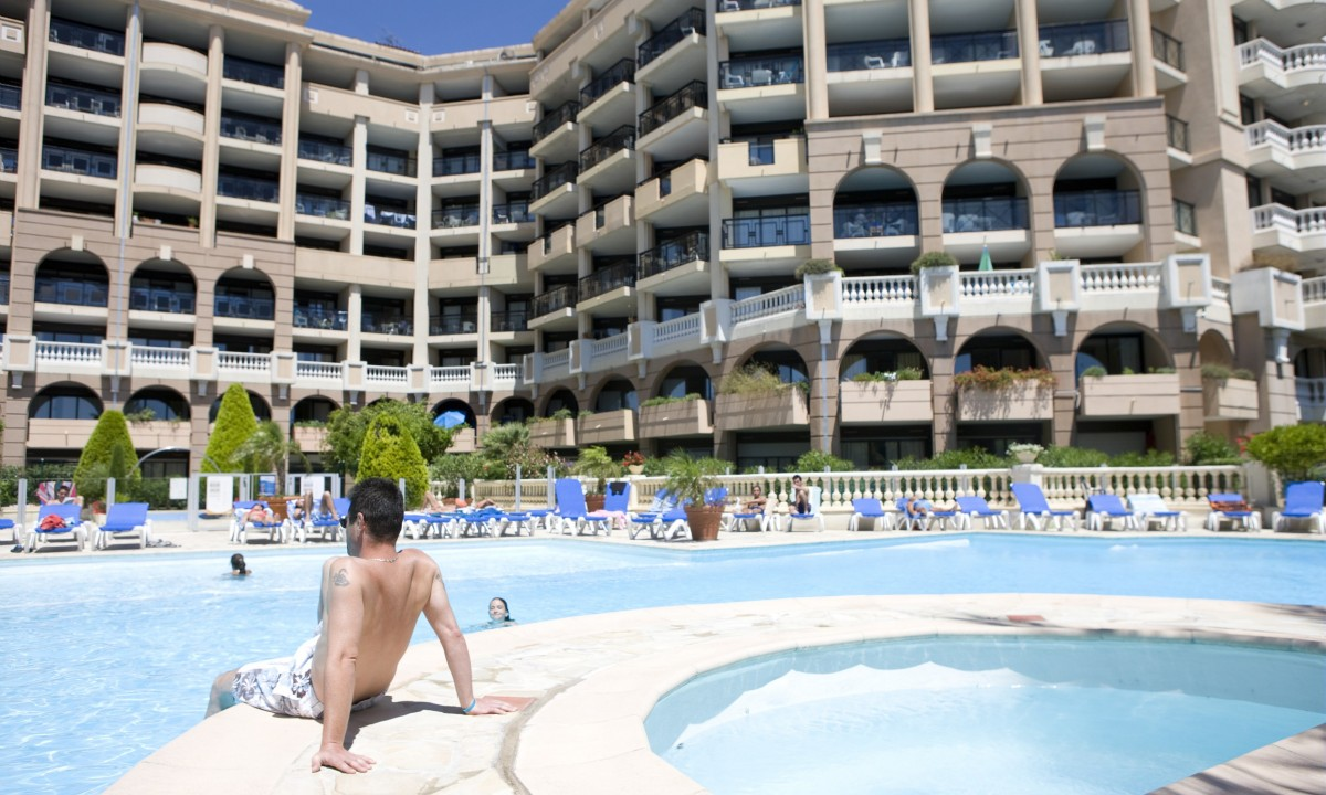 Mand ved poolen foran ferielejlighederne