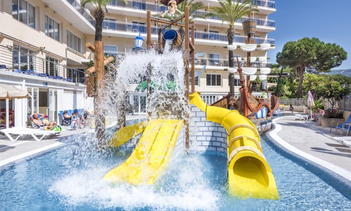 Gul rutsjebane i pool med hotel bagved