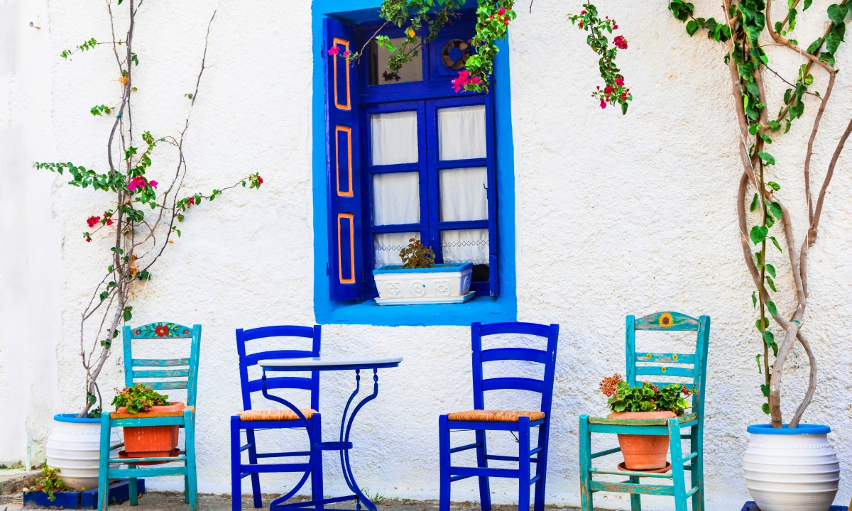 Idyllisk graesk hus i blaa og hvide farver