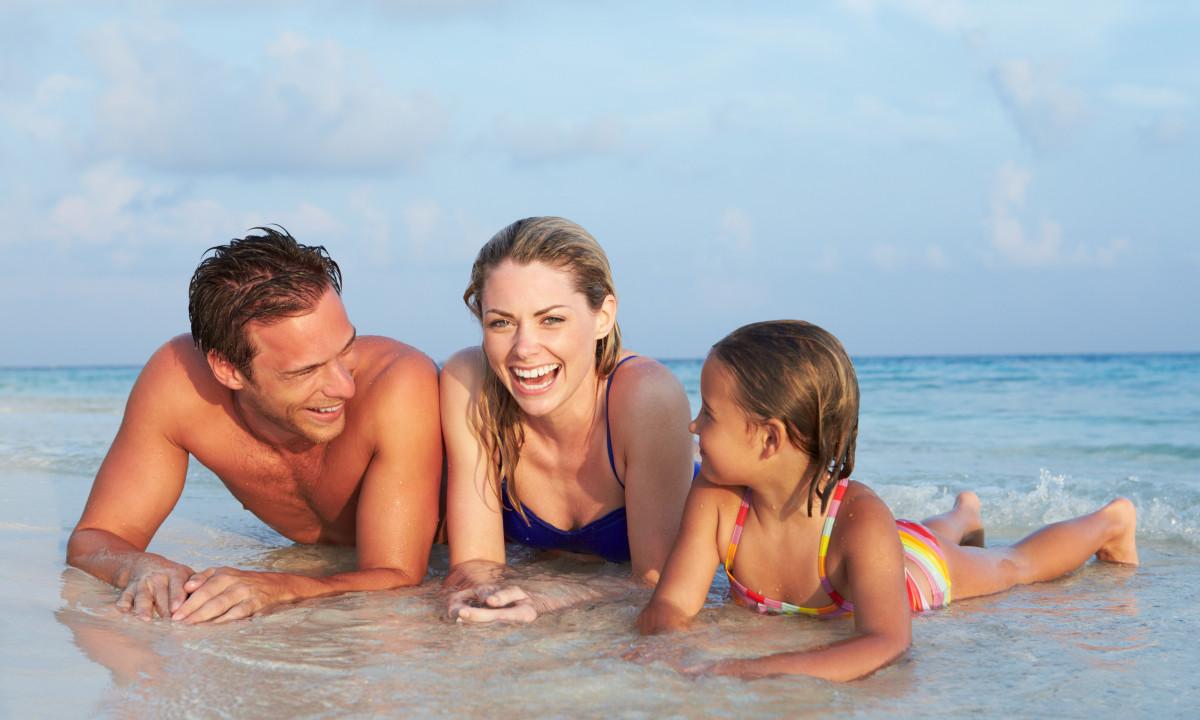 Familie på tre i strandkanten