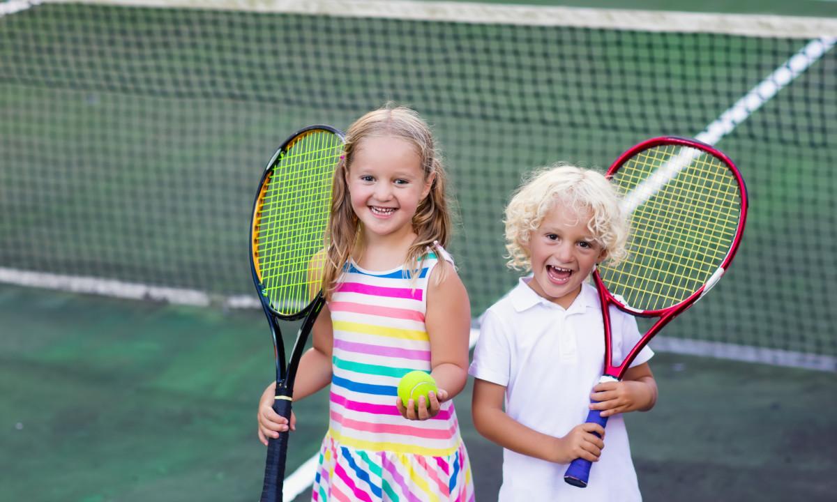 Glade børn der spiller tennis