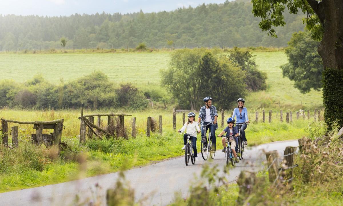 Familie på cykletur i naturen - Far, mor og boern cykler