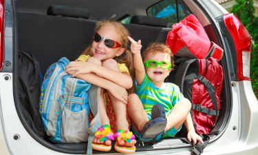 Børn i bils bagagerum med bagage