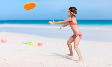 Pige leger med frisbee på stranden
