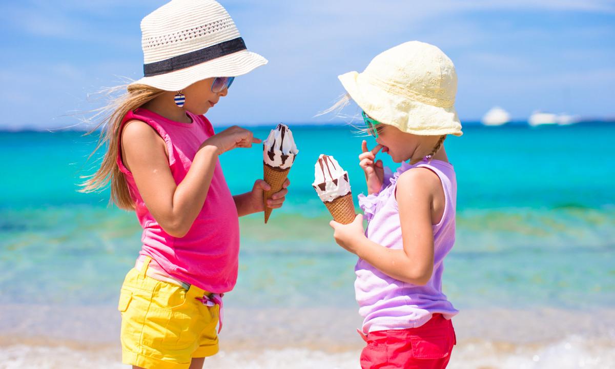 Piger nyde en is på stranden