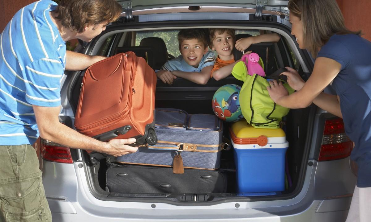 Rejse - Familie pakker bagage i bil til ferien