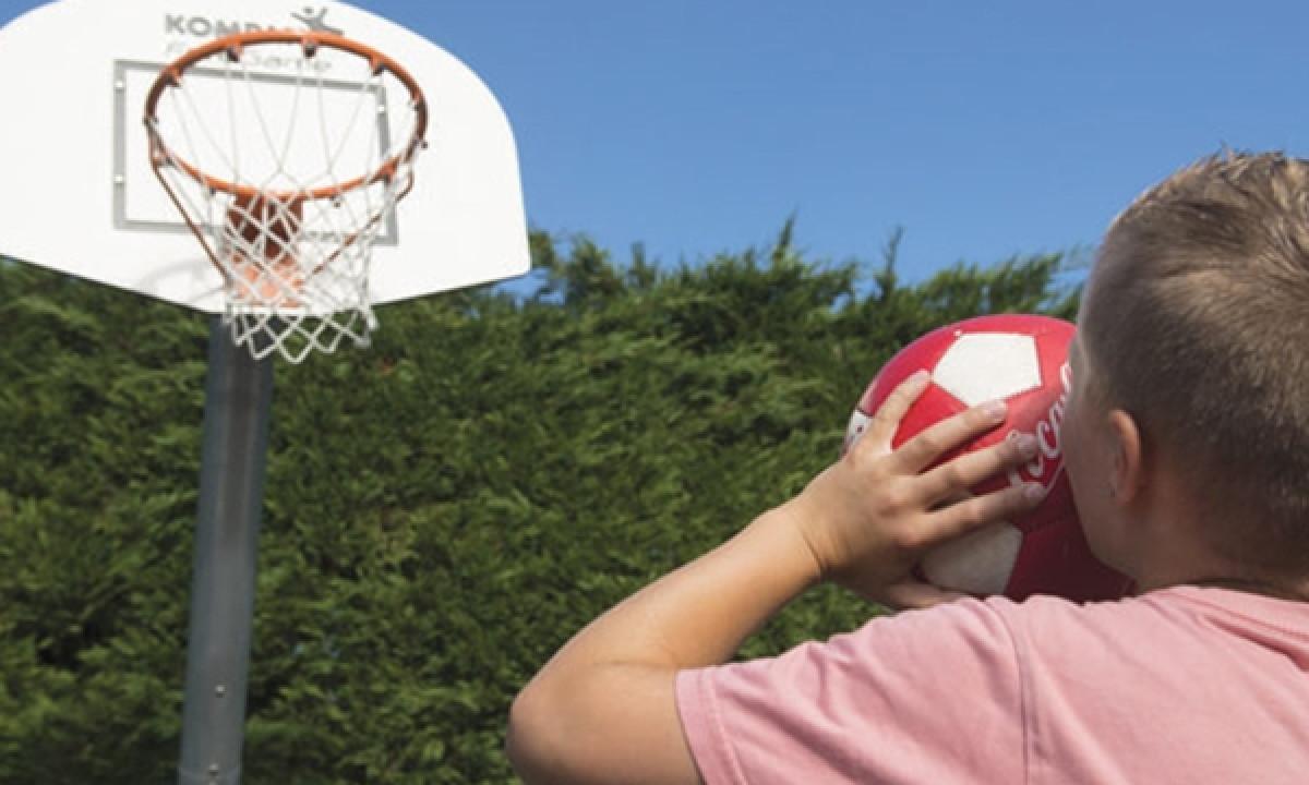 Dreng spiller basket på pladsen