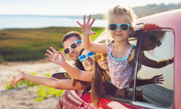 Familie vinker fra bilen